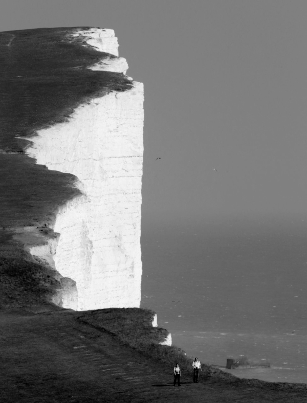 A couple walk along the Seven Sisters cliffs close to the Beachy Head lighthouse near Eastbourne, in southern England